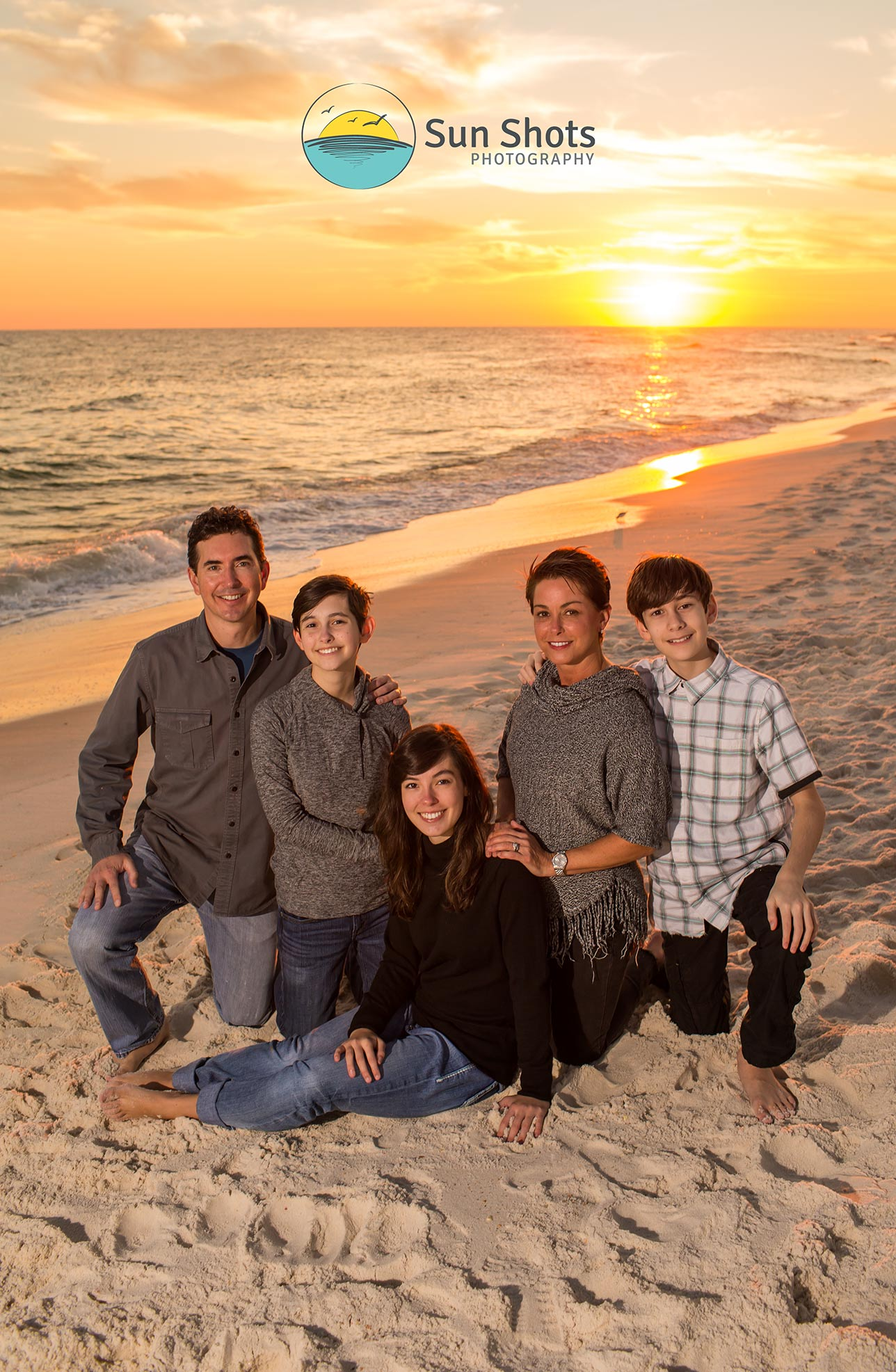 Family portrait on beach with sunsetting behind them over the ocean.