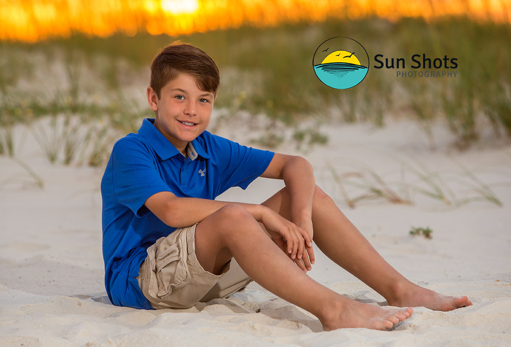 Boy posing for picture on beach with sunrise in background
