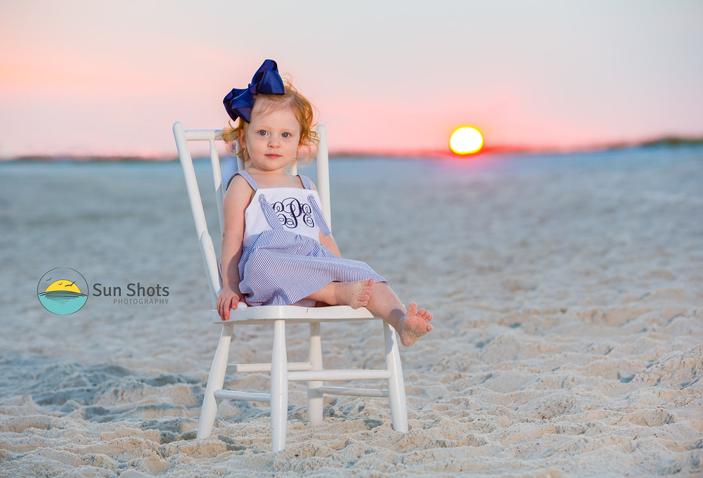 Young girl sitting in chair on beach with sunset in background