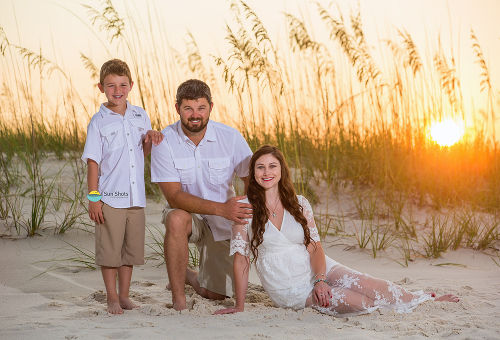 Family of three posing for picture with sunrise in the background