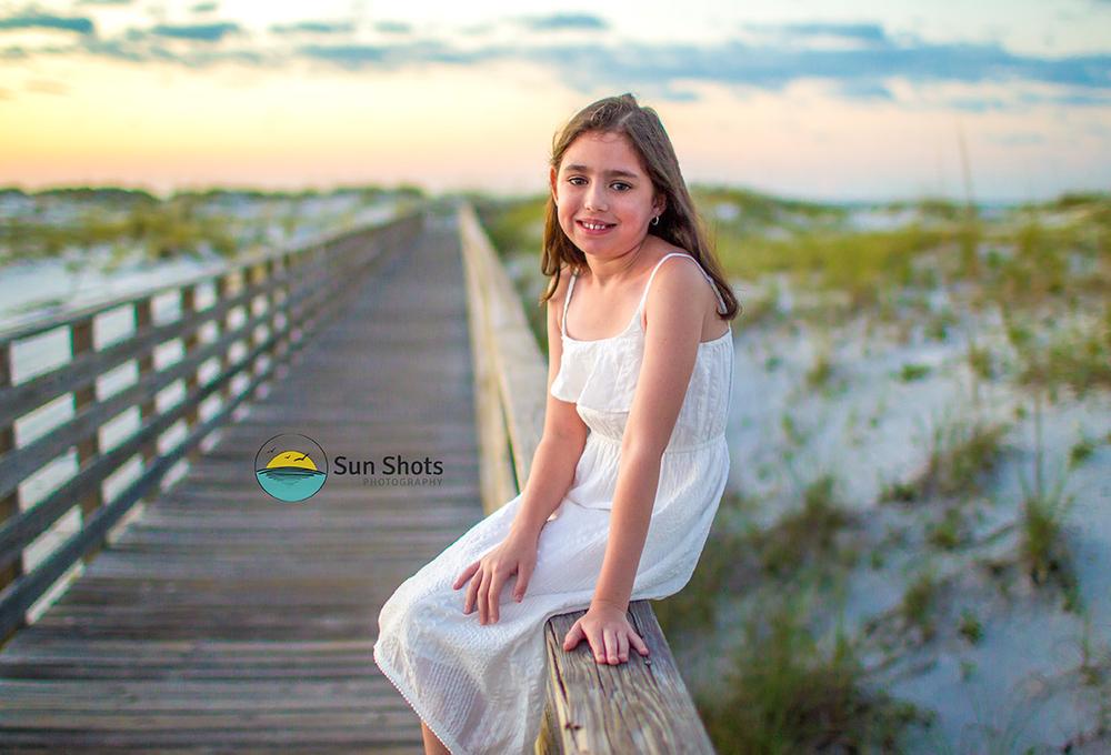 Young girl sitting on boardwalk posing for picture