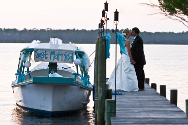 Couple kissing as the depart on boat for honeymoon