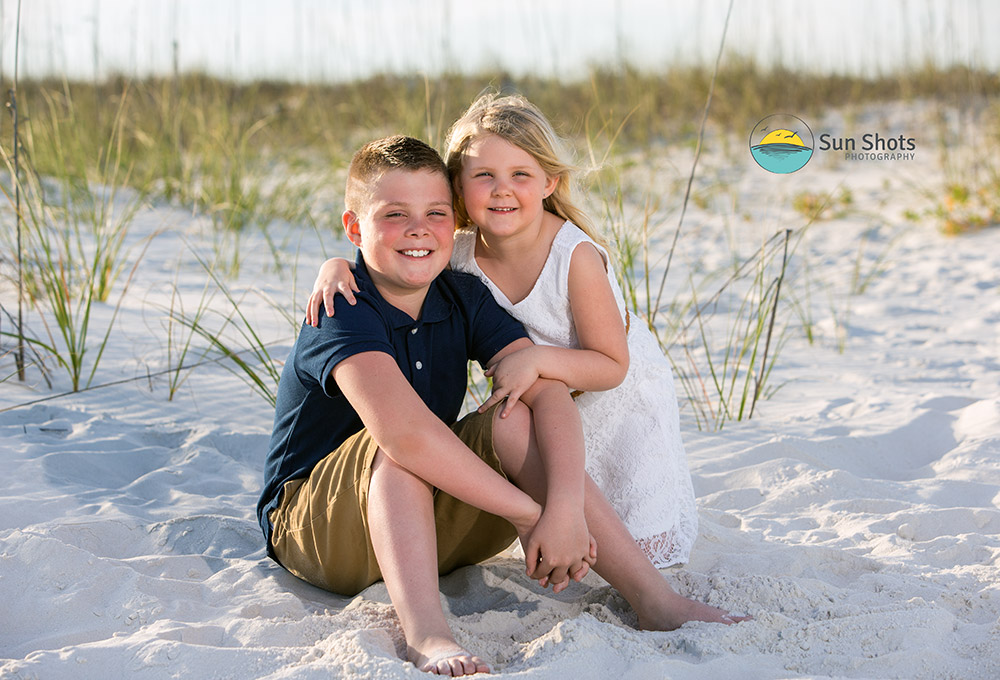 Siblings posing for picture on beach