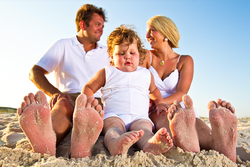 Small family sitting in sand with sandy feet
