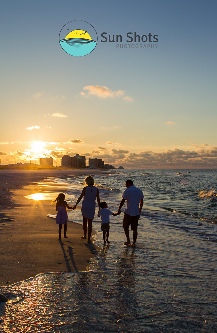 Family walking onto the beach into the sunset