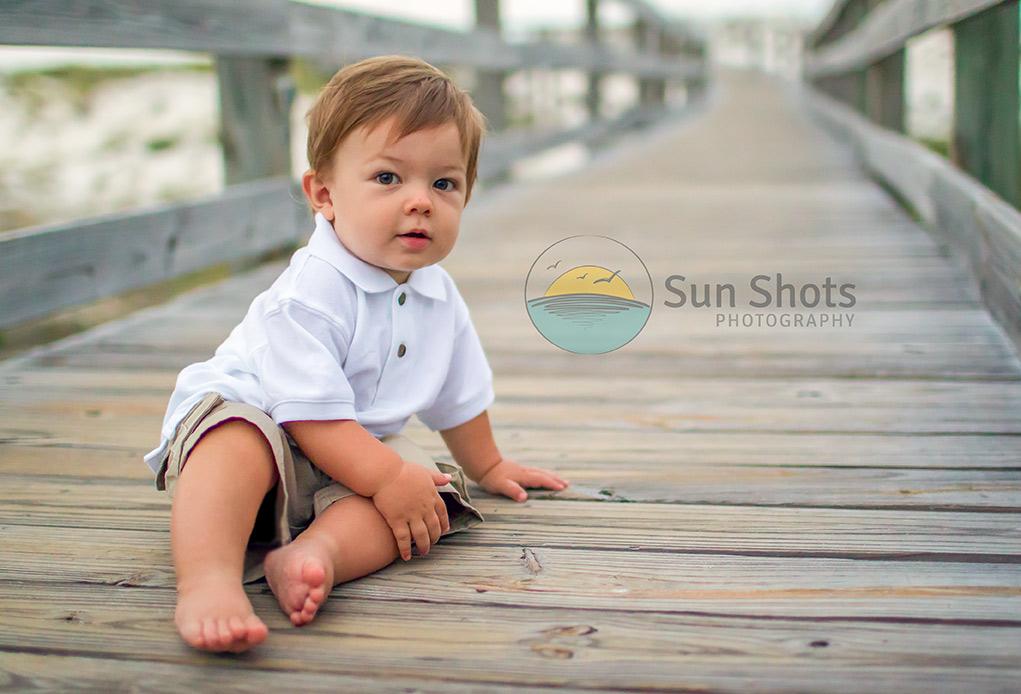 Little boy sitting on boardwalk posing for portrait