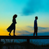 Image of two teenager siblings walking on boardwalk rail at sunrise