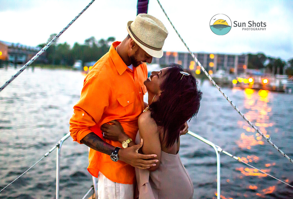 Couple hugging on front of sail boat