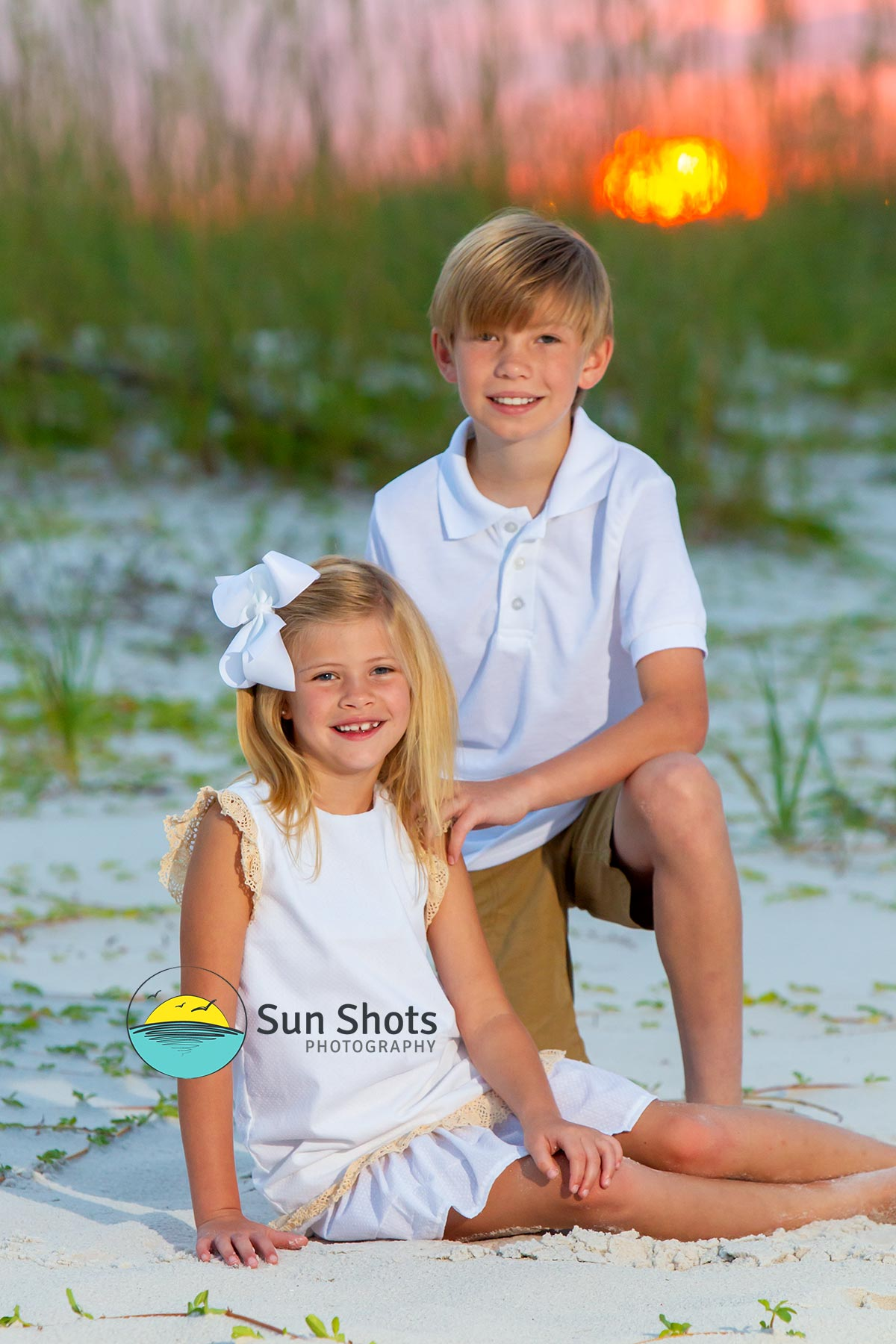 Two children posing for sunrise beach picture