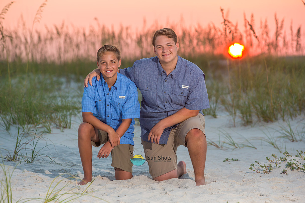 Two brothers enjoying a sunrise family beach photo session.