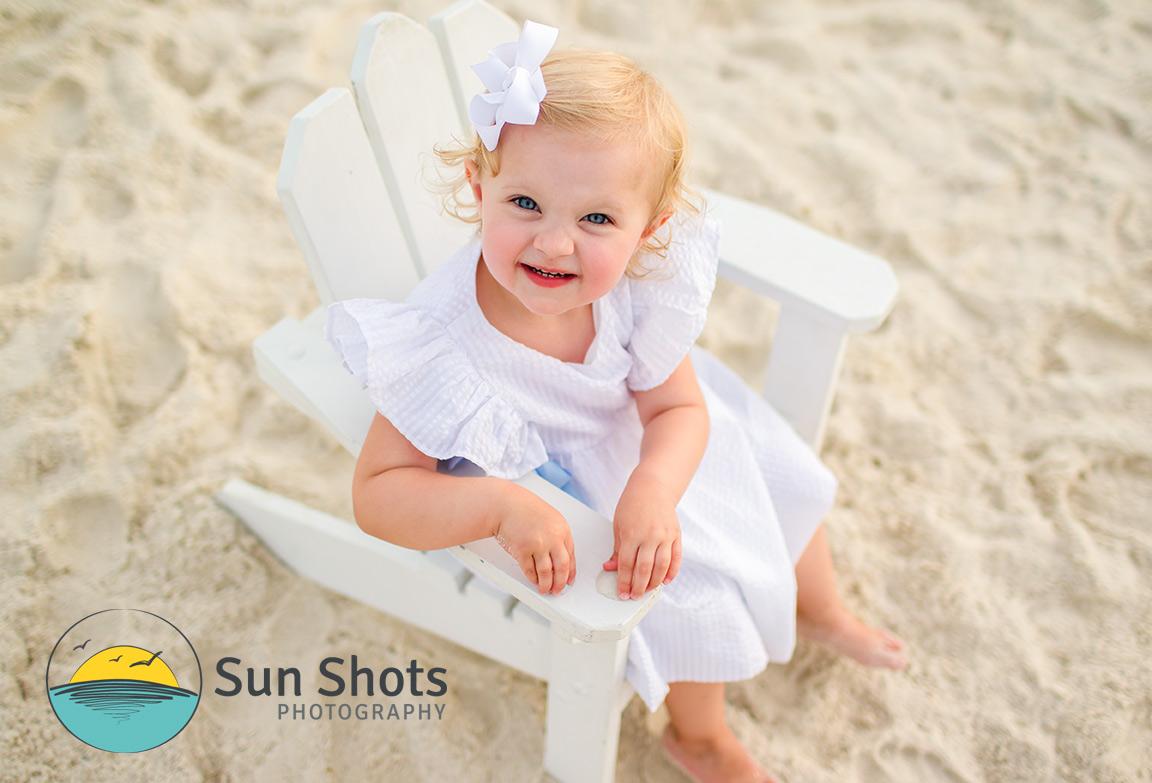 Child on beach sitting in wooden chair
