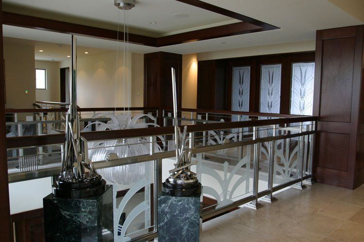 Art Deco glass panels in stainless steel rails supporting etched-carved art glass. System designed by Classical glass studios, De Carter Ray.