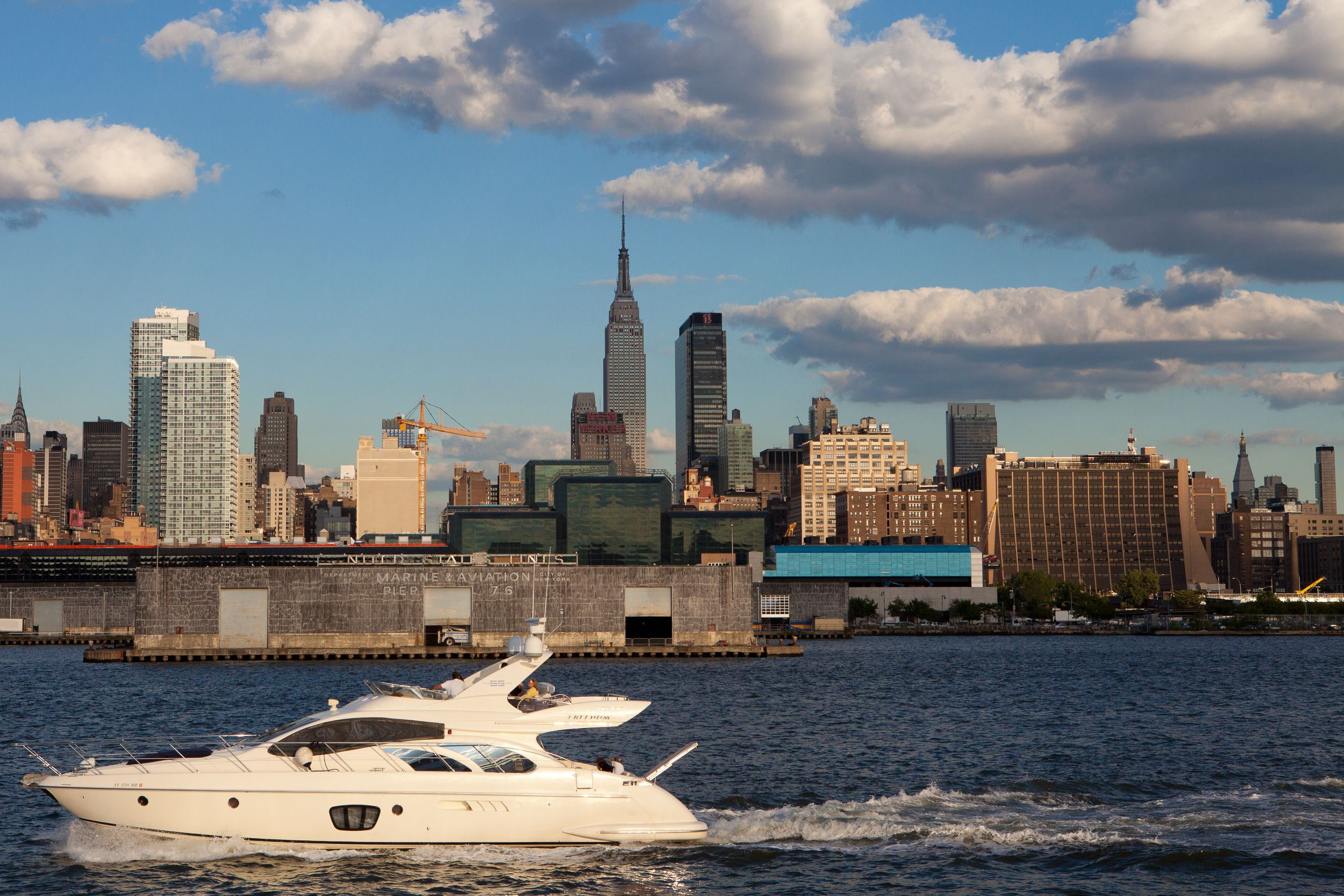 Watercraft and Empire State Building as seen from the Hudson River