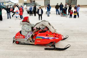 Innuit elder riding a snow machine with wolf skin