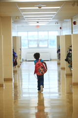 Student with backpack in hallway