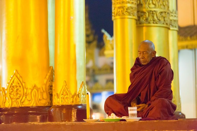 Monk worshipping at Shwedagon Pagoda at night.