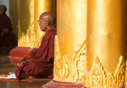 Monk sitting amidst the golden columns of Shwedagon Pagoda