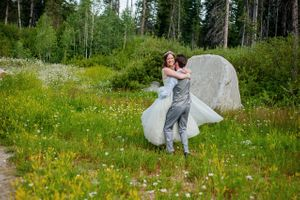Ashley_Dan_Solitude_Resort_Solitude_Utah_Bride_Groom_Embracing_in_Mountain_Field_with_Mountain_Flowers.jpg