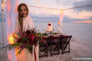 Salt_Air_Wedding_Shoot_Saltair_Resort_Salt_Lake_City_Utah_Elegant_Table_Setting_Candlelit_Head_Table_Bride_Holding_Bouquet.jpg