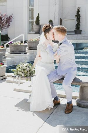 Lexie_Neil_Utah_State_Capitol_Salt_Lake_City_Utah_Bride_Groom_Kissing_on_Bench_By_Fountain.jpg