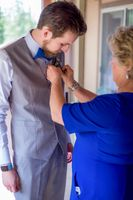 Ashley_Dan_Solitude_Resort_Solitude_Utah_Grooms_Mother_Putting_Boutonniere_on_Groom.jpg