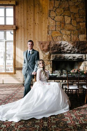 Rocky_Mountain_Bride_Winter_Elopement_Deer_Valley_Empire_Lodge_Deer_Valley_Resort_Park_City_Utah_Classic_Pose_Groom_Standing_Bridge_Sitting.jpg