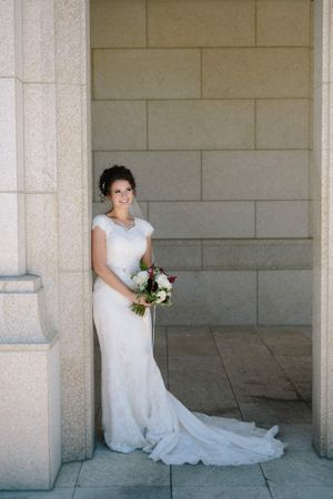Chloe_Austin_Ben_Lomond_Suites_Ogden_Utah_Great_Gatsby_Smiling_Bride_Leaning_Against_Pillar.jpg
