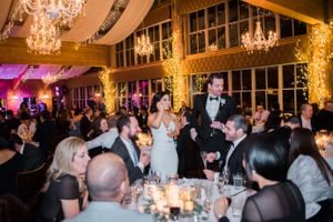 Julia_Mark_Silver_Lake_Lodge_Deer_Valley_Resort_Park_City_Utah_Bride_Groom_Greeting_Guests_Under_Softly_Lit_Chandelier_and_Ceiling.jpg