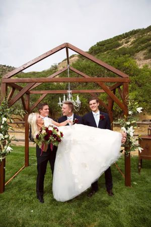 Tori_Sterling_Quiet_Meadow_Farms_Mapleton_Utah_Bride_Laying_on_Groom_Groomsmens_Arms.jpg