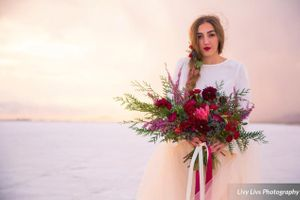Salt_Air_Wedding_Shoot_Saltair_Resort_Salt_Lake_City_Utah_Bride_with_Bouquet_Sun_Peeking_Through_Clouds.jpg